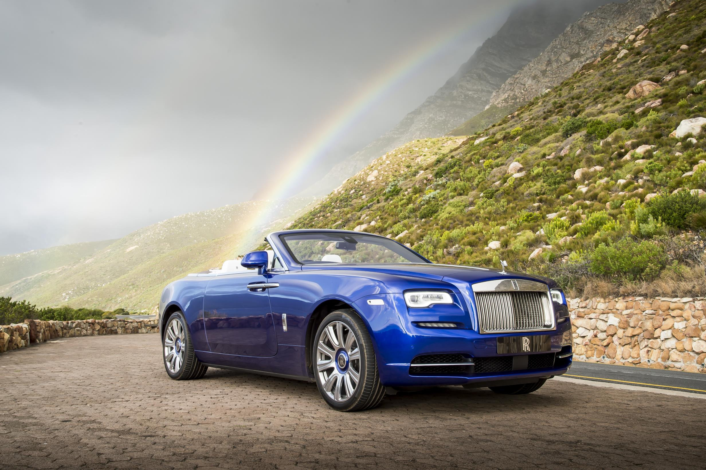 Brigjt blue metallic Rolls Royce Dawn convertible parked with a rainbow behind it